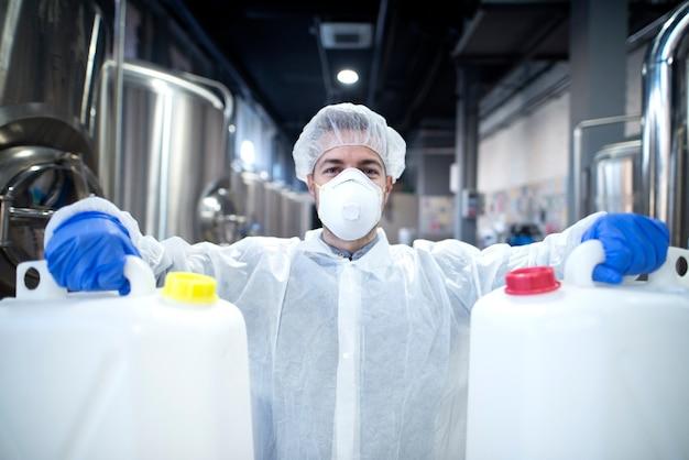 Trabajador industrial con máscara protectora y uniforme blanco sosteniendo latas de plástico para la industria química