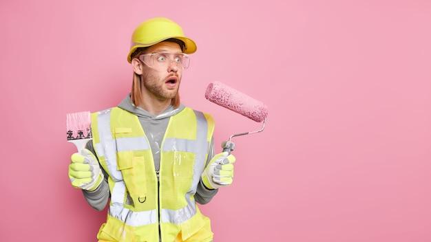 El trabajador industrial masculino asustado hace la reparación en el apartamento sostiene el rodillo de pintura y el cepillo mira hacia otro lado con expresión de asombro