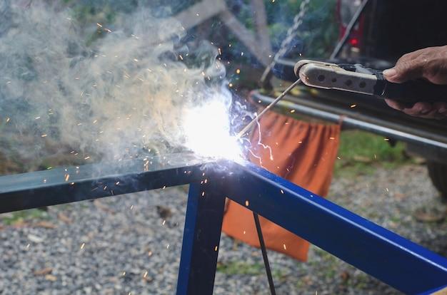 Trabajador industrial en el primer plano de soldadura de fábrica sin seguridad