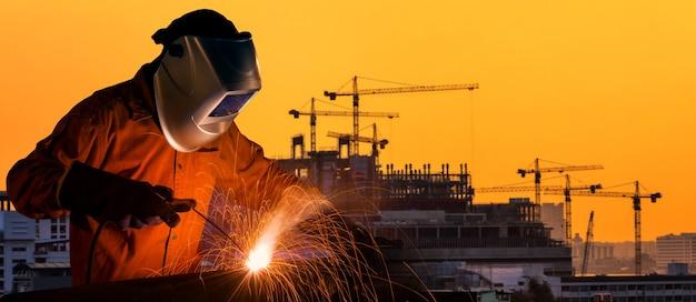 Trabajador industrial que suelda con autógena la estructura de acero para con el emplazamiento de la obra en fondo.