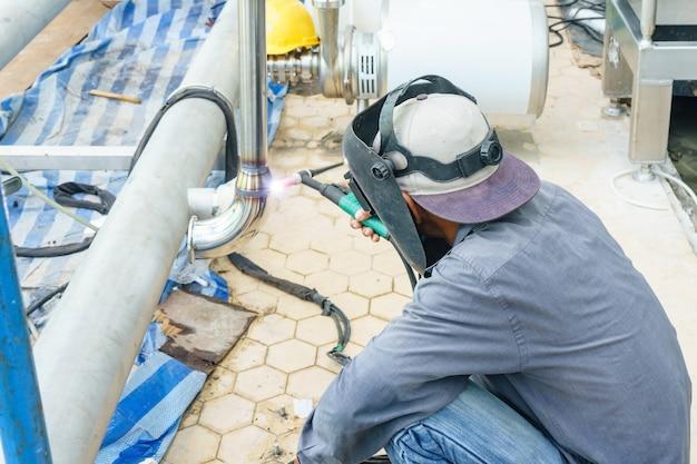 Trabajador industrial que suelda los tubos de acero inoxidables con el argón, primer de la máscara de soldadura