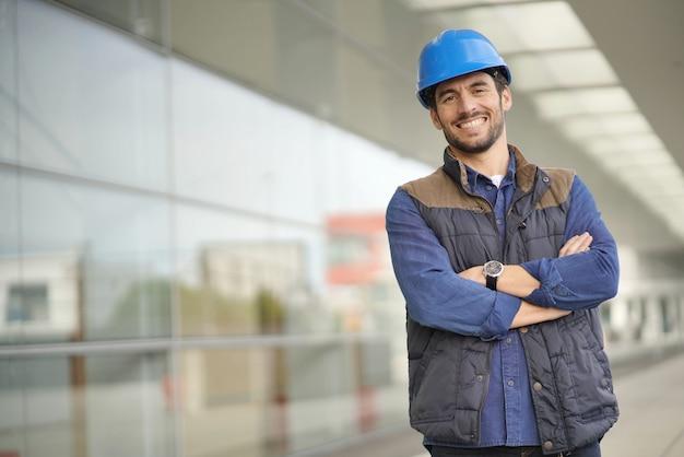 Trabajador industrial sonriente en el casco delante del edificio moderno