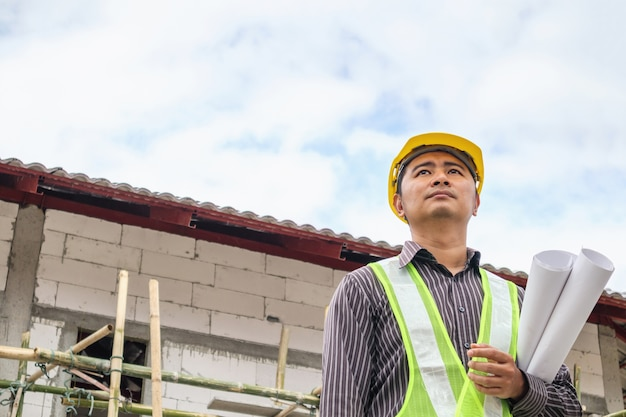 Trabajador de ingeniero de construcción de hombre de negocios asiático en casco protector y papel de planos en mano en el sitio de construcción de viviendas
