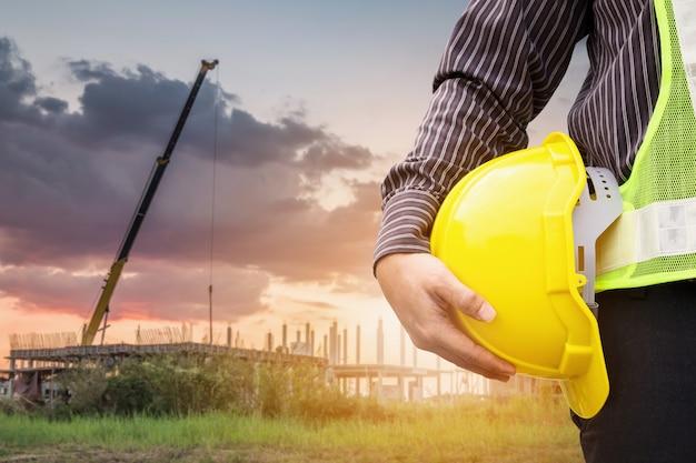 Trabajador de ingeniero de construcción de hombre de negocios asiáticos en casco protector y papel de planos