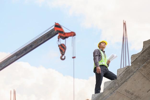 Trabajador de ingeniero de hombre de negocios en casco protector y papel de planos en mano en el sitio de construcción