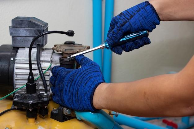 Trabajador ingeniero mantenimiento reparación gasget valor de bomba de agua