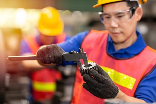 Trabajador ingeniero que usa vernier caliper para verificar el tamaño del engranaje para precisión, precisión, control de calidad de la pieza de servicio en fábrica