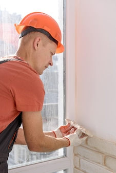 Un trabajador está instalando baldosas de ladrillo de yeso en la pared.