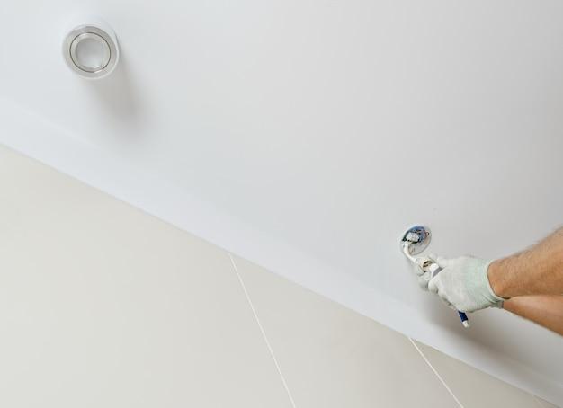 Un trabajador está instalando un foco led en el techo suspendido.