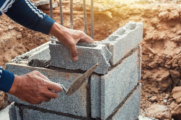 Trabajador instalando ladrillos en sitio de construcción