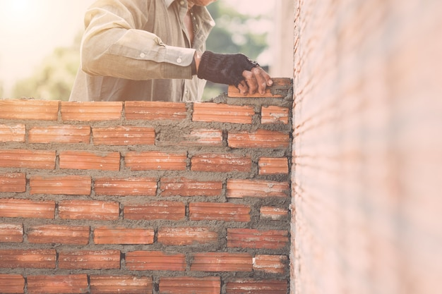 Trabajador instalando paredes de ladrillos en proceso de construcción de viviendas