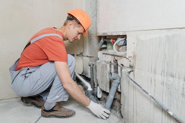 El trabajador está instalando tuberías de alcantarillado.