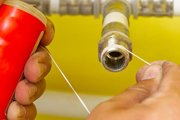Trabajador instalar cinta de sellado para accesorios de tubería de agua. plomero poniendo cinta de sellado en una rosca de un accesorio de plomería