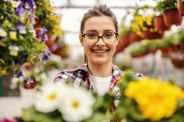 Trabajador de jardín de vivero positivo sonriente sosteniendo flores.