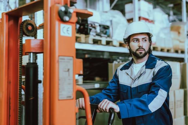 Trabajador joven almacén barbudo conduciendo carretilla elevadora
