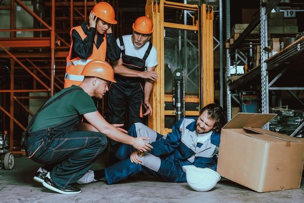 Trabajador joven del almacén herida pierna en el lugar de trabajo