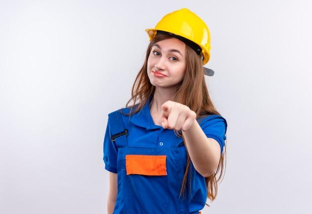 Trabajador joven constructor en uniforme de construcción y casco de seguridad mirando confiado apuntando con el dedo índice