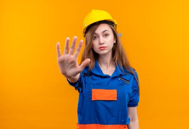 Trabajador joven constructor en uniforme de construcción y casco de seguridad de pie con la mano abierta haciendo señal de stop