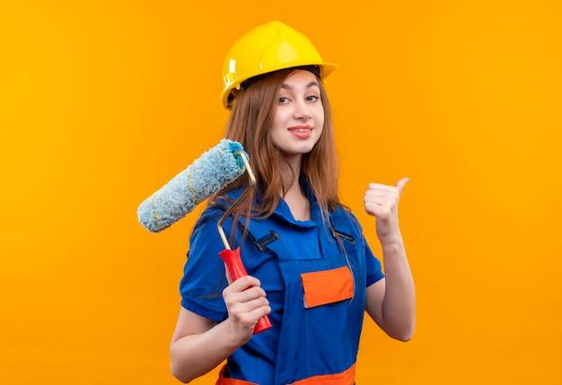 Trabajador joven constructor en uniforme de construcción y casco de seguridad con rodillo de pintura mostrando los pulgares para arriba sonriendo confiado de pie sobre la pared naranja