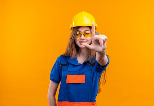 Trabajador joven constructor en uniforme de construcción y casco de seguridad sonriendo mostrando el dedo índice en la parte delantera