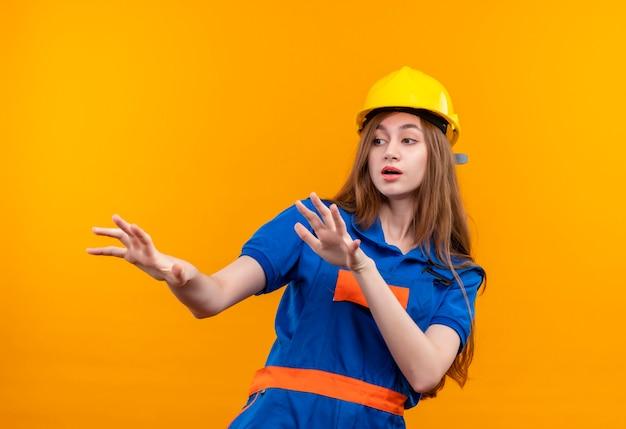 Trabajador joven constructor en uniforme de construcción y casco de seguridad sosteniendo las palmas hacia arriba haciendo gesto de defensa de pie sobre la pared naranja