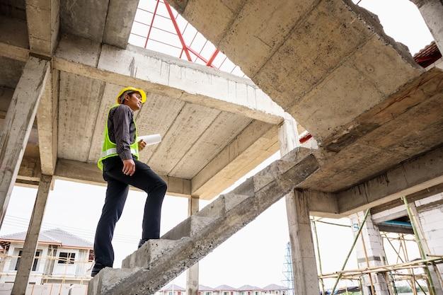 Trabajador joven ingeniero profesional en casco protector y papel de planos en mano en el sitio de construcción de edificios de viviendas