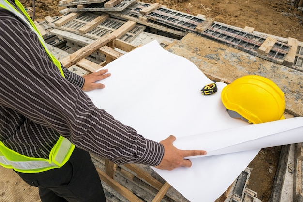 Trabajador de joven ingeniero profesional de hombre de negocios en el sitio de construcción de edificios de viviendas con plano