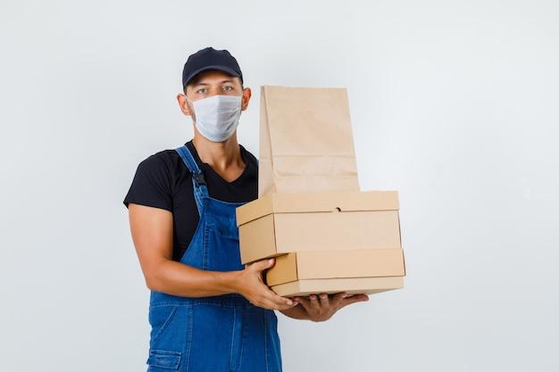 Trabajador joven sosteniendo cajas de cartón y bolsa de papel en uniforme, máscara, vista frontal.