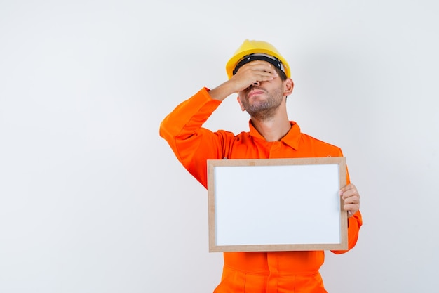 Trabajador joven en uniforme con marco en blanco con la mano en los ojos.