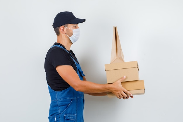 Trabajador joven en uniforme, máscara sosteniendo cajas de cartón y bolsa de papel y mirando serio.