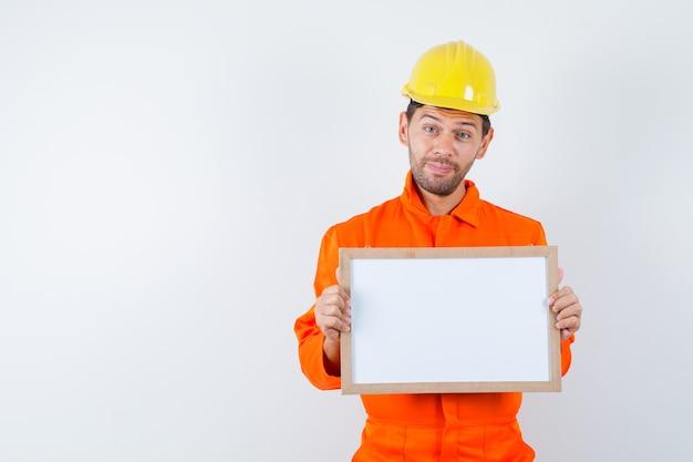 Trabajador joven en uniforme que sostiene el marco en blanco y parece alegre.
