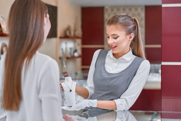 Trabajador de joyería rubia que presenta un hermoso collar a una mujer en una joyería
