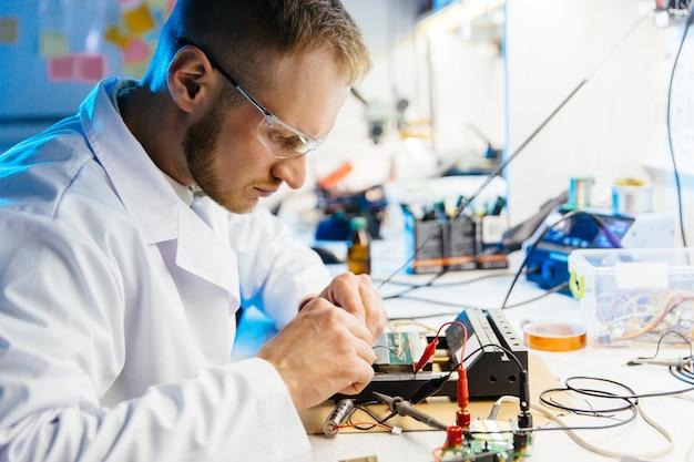 El trabajador de laboratorio electrónico conecta la placa de circuito con cables y abrazaderas para realizar pruebas y mediciones