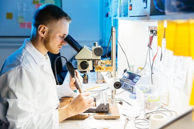 Trabajador de laboratorio electrónico trabajando con microscopio.