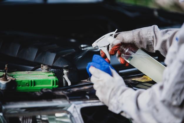 Trabajador de lavado de autos con un uniforme blanco de pie con una esponja para limpiar el automóvil en el centro de lavado de automóviles, concepto para la industria del cuidado del automóvil.