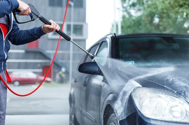 Trabajador de lavado de coches profesional está lavando el coche del cliente