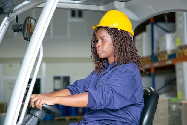 Trabajador logístico femenino joven serio en uniforme protector que conduce la carretilla elevadora en el almacén