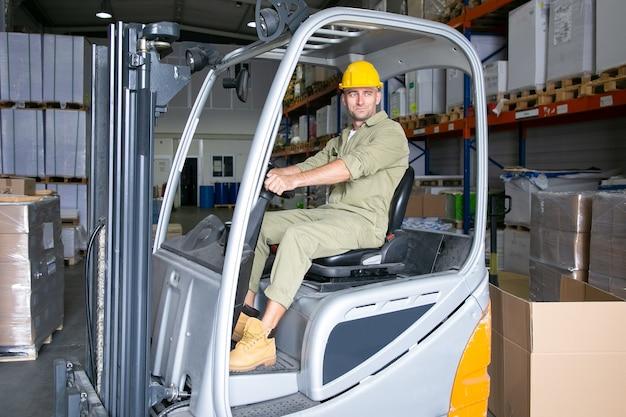 Trabajador logístico masculino positivo en casco de conducción de montacargas en almacén, sonriendo, mirando a otro lado