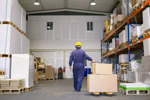 Trabajador logístico senior en casco y uniforme caminando en el almacén, gato de paleta de ruedas. vista posterior, de cuerpo entero. concepto de trabajo y logística