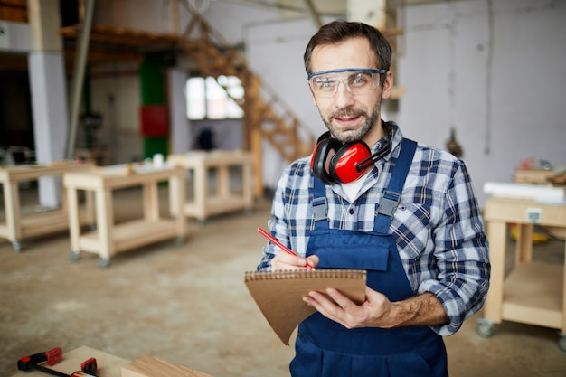Trabajador maduro tomando notas en fábrica