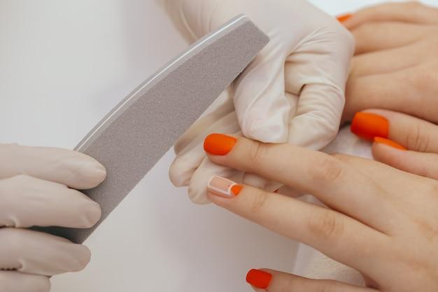 Trabajador de manicura alisando uñas de clientes con lima de uñas
