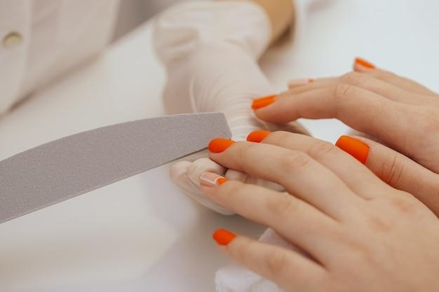 Trabajador de manicura alisando las uñas de los clientes con lima de uñas.