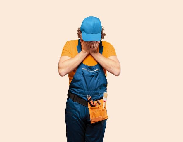 Trabajador de manitas que cubre su cara