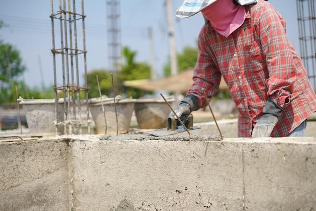 Trabajador de mano de obra construyendo muro con cemento de concreto