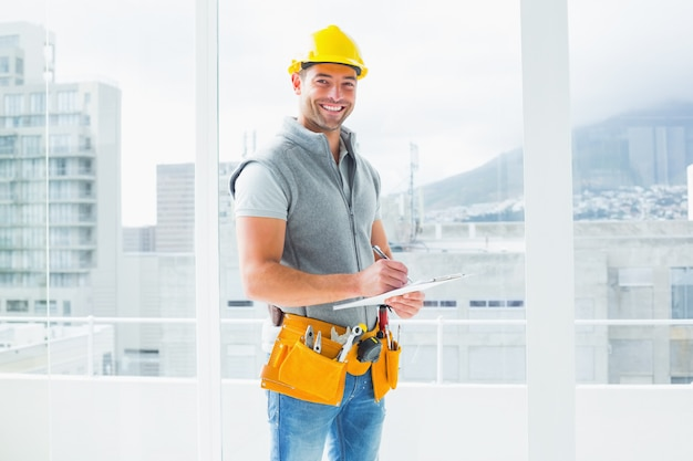 Trabajador manual escribiendo en el portapapeles en el edificio