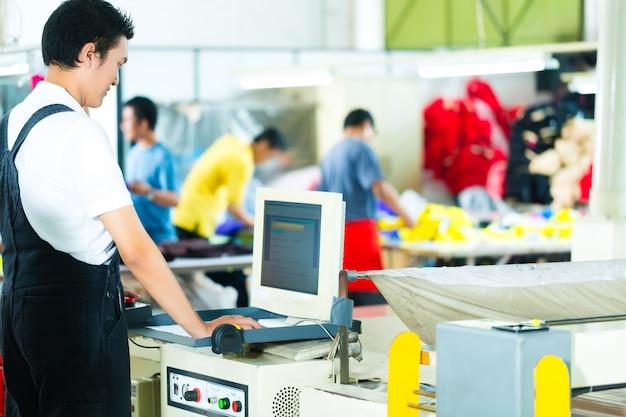 Trabajador en una máquina en fábrica asiática
