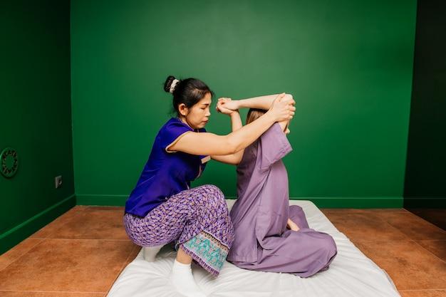 Trabajador masajista tailandés en ropas étnicas asiáticas hace procedimientos de spa tradicionales a la bella dama blanca en pijama morado en la sala de yoga verde