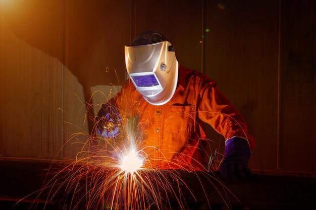 Trabajador con máscara protectora de soldadura de metal en almacén industrial.