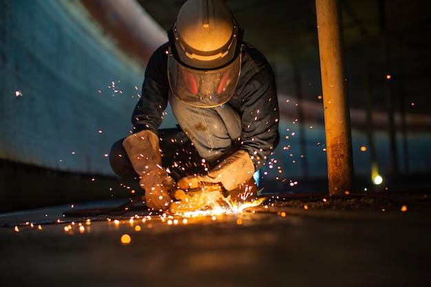 Trabajador masculino chispa de corte de metal en la placa de acero del fondo del tanque con destello de luz de corte de cerca, use guantes protectores y máscara en el espacio confinado lateral.