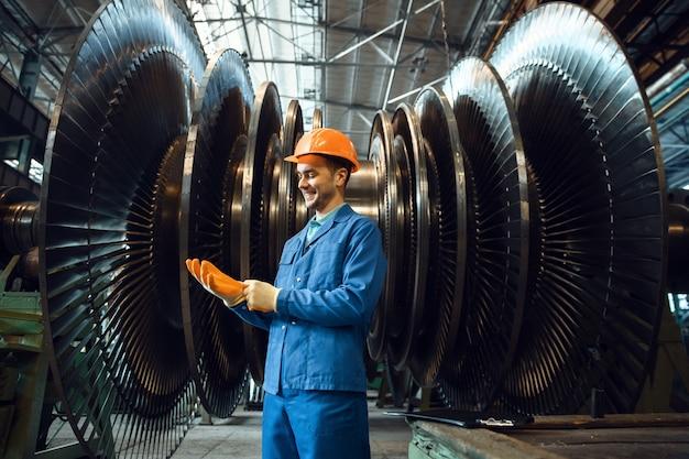 Trabajador masculino comprueba las paletas del impulsor de la turbina en la fábrica.
